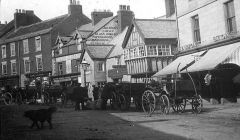 carts loading and unloading by stables in Newgate Street Morpeth 1900.JPG